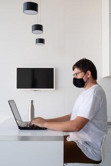 Młody mężczyzna w czarnej masce ochronnej pracujący z laptopem w domu