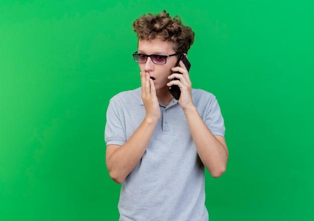 Młody mężczyzna w czarnych okularach na sobie szarą koszulkę polo rozmawia przez telefon komórkowy jest zdumiony i zaskoczony zielenią