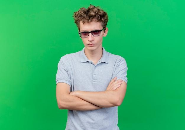 Młody mężczyzna w czarnych okularach na sobie szarą koszulkę polo z poważną twarzą ze skrzyżowanymi rękami na piersi na zielono