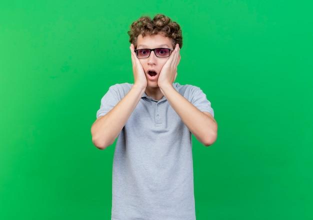 Młody mężczyzna w czarnych okularach na sobie szarą koszulkę polo z rękami na twarzy jest w szoku na zielono