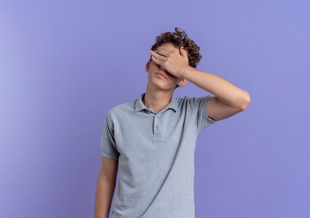 Młody mężczyzna w czarnych okularach na sobie szarą koszulkę polo zasłaniającą oczy ręką zmęczoną i znudzoną stojącą nad niebieską ścianą