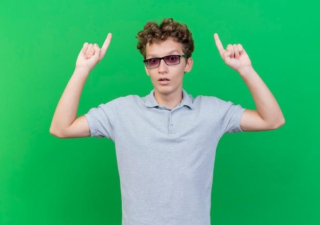 Młody mężczyzna w czarnych okularach ubrany w szarą koszulkę polo, podnosząc obie ręce pokazując palce wskazujące, zaskoczony stojąc nad zieloną ścianą