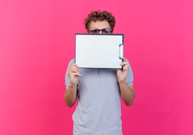 Młody mężczyzna w czarnych okularach ubrany w szarą koszulkę polo trzymający schowek z pustymi stronami, chowający za nim twarz, zerkający nad stojącą nad różową ścianą