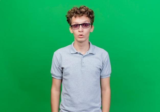 Młody mężczyzna w czarnych okularach ubrany w szarą koszulkę polo zaskoczony i zdumiony stojąc nad zieloną ścianą