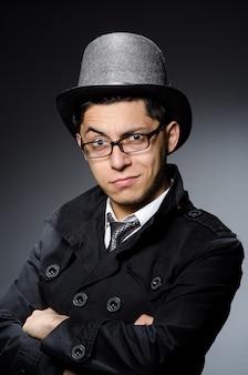 Młody mężczyzna w czarnym płaszczu i kapeluszu na szarym