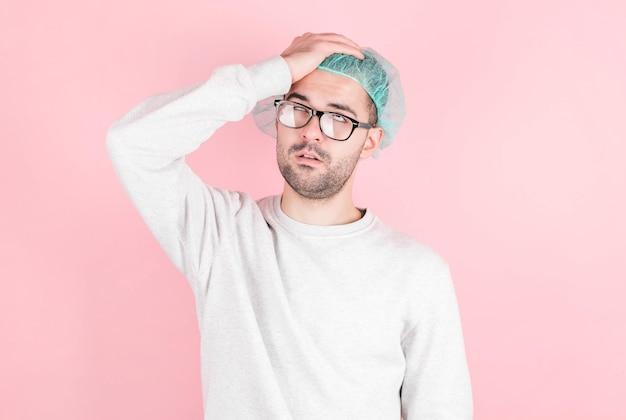 Młody mężczyzna w czepku lekarskim i okularach mdleje podczas porodu na różowej ścianie, trzyma głowę, przewraca oczami. pojęcie procesu porodu.