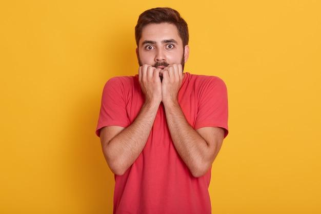 Młody mężczyzna w czerwonej koszulce stojący na żółtym tle, facet wyglądający na przestraszonego, o zdumionym wyrazie z rękami pod brodą, gryzie palec, widzi coś strasznego.