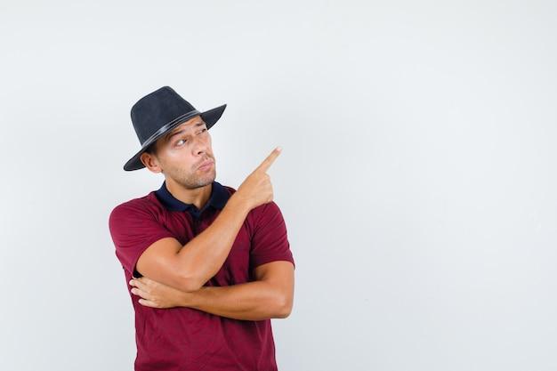 Młody mężczyzna w czerwonej koszuli, czarny kapelusz wskazujący i wyglądający na zainteresowanego, widok z przodu.