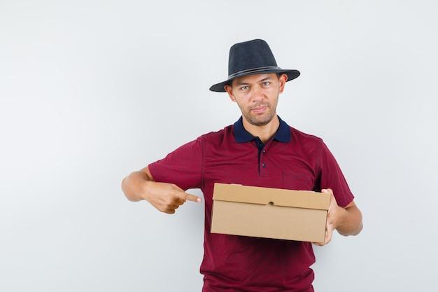 Młody mężczyzna w czerwonej koszuli, czarny kapelusz wskazujący na pudełka i wyglądający na zainteresowanego, widok z przodu.
