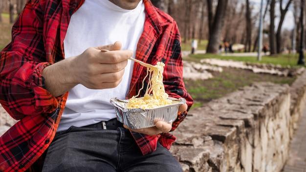 Młody mężczyzna w czerwonej koszuli je makaron w parku