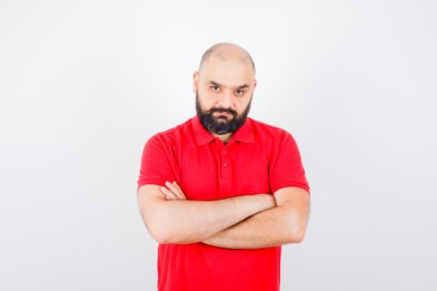 Młody mężczyzna w czerwonej koszuli stojący ze skrzyżowanymi rękami, widok z przodu.