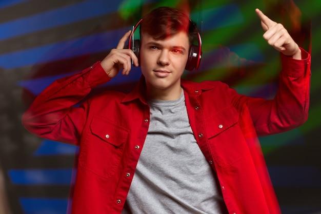 Młody mężczyzna w czerwonej koszuli ze słuchawkami słucha muzyki