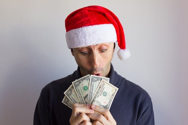 Młody mężczyzna w czerwonym kapeluszu bożonarodzeniowym, trzymający wentylator banknotów dolarowych z zaskoczonym spojrzeniem na białym tle