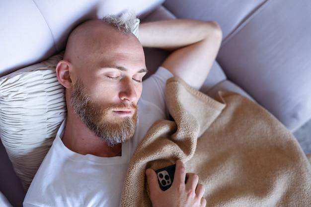 Młody mężczyzna w domu zasnął na kanapie z telefonem komórkowym