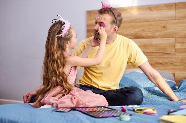 Młody mężczyzna w domu ze swoją małą uroczą dziewczynką, zrób makijaż twarzy przy użyciu kosmetyków dekoracyjnych matki.