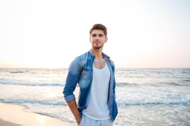 Młody mężczyzna w dżinsowej koszuli stojący na plaży