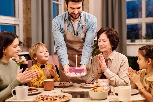 Młody mężczyzna w fartuchu stawia talerz z przeszklonym domowym ciastem z płonącą świeczką na serwowanym stole przed świątecznym obiadem z rodziną