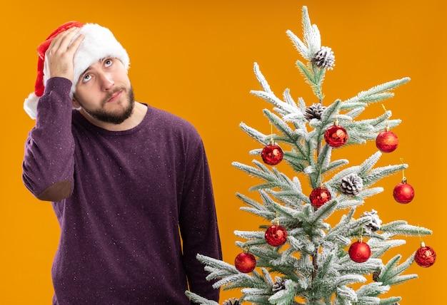 Młody mężczyzna w fioletowym swetrze i czapce mikołaja wygląda na zdezorientowanego i bardzo niespokojnego stojącego obok choinki na pomarańczowym tle