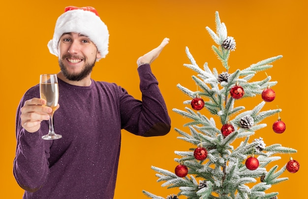 Młody mężczyzna w fioletowym swetrze i santa hat trzyma kieliszek szampana patrząc na aparat uśmiechnięty obok choinki na pomarańczowym tle