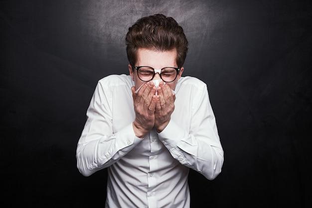 Młody mężczyzna w formalnej białej koszuli i nerdowych okularach zakrywających usta chusteczką podczas kichania na czarnym tle