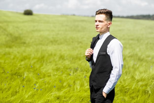 Młody mężczyzna w formalnym garniturze na zielonym polu