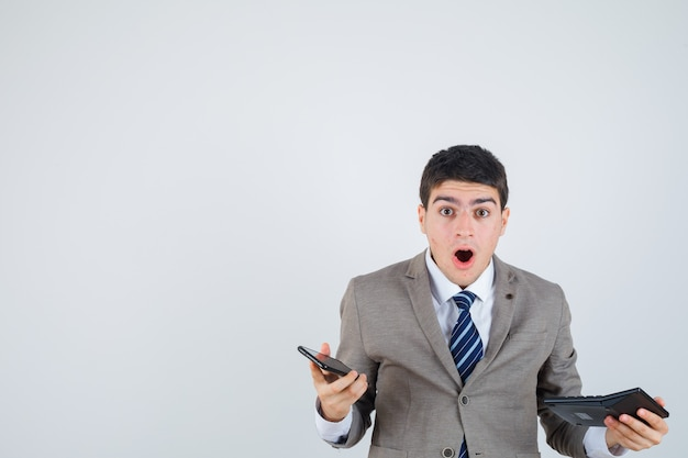 Młody mężczyzna w formalnym garniturze trzyma telefon i kalkulator i wygląda na zaskoczonego