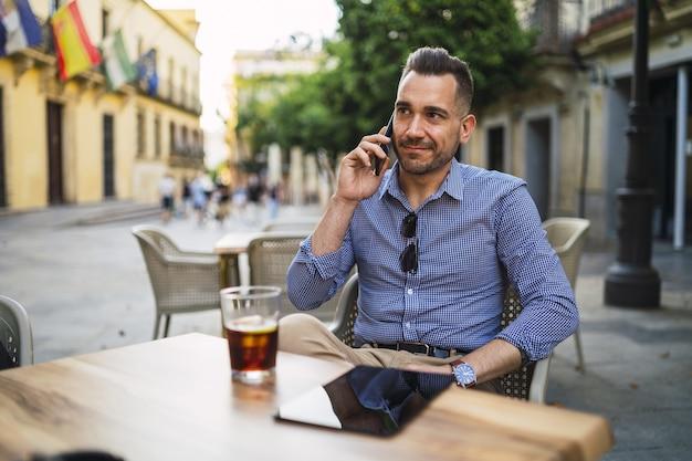 Młody mężczyzna w formalnym stroju siedzi w kawiarni na świeżym powietrzu rozmawia przez telefon