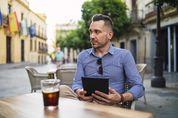 Młody mężczyzna w formalnym stroju siedzi w kawiarni na świeżym powietrzu, trzymając tabletkę i pije zimny napój