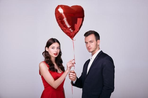 Młody mężczyzna w garniturze i kobieta w czerwonej sukience trzyma balon w kształcie czerwonego serca na białym tle