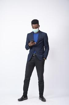 Młody mężczyzna w garniturze i masce na twarz, używający swojego telefonu komórkowego