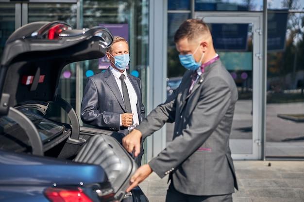 Młody mężczyzna w garniturze i masce pakujący bagaż biznesmena do bagażnika samochodu po przybyciu na lotnisko