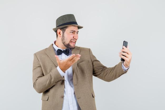 Młody mężczyzna w garniturze, krzyczy podczas rozmowy wideo i wygląda na sfrustrowanego, widok z przodu.
