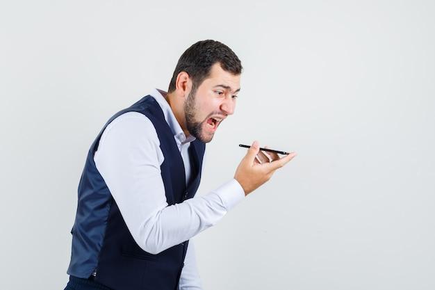 Młody mężczyzna w garniturze nagrywa wiadomość głosową w kamizelce i patrzy na zły