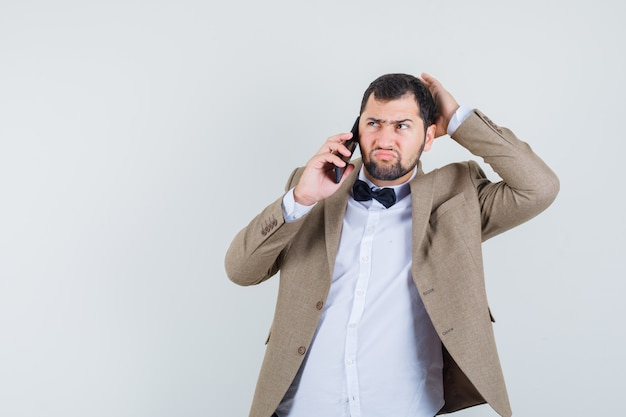 Młody mężczyzna w garniturze rozmawia przez telefon komórkowy i niezdecydowany, widok z przodu.