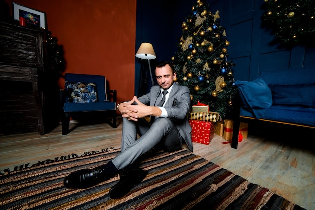 Młody mężczyzna w garniturze siedzi na podłodze pod choinką
