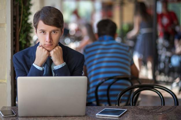 Młody mężczyzna w garniturze siedzi w biurze