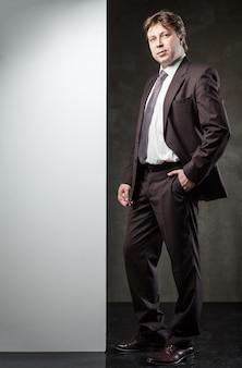 Młody mężczyzna w garniturze z banerem na tekst na szarym tle grunge