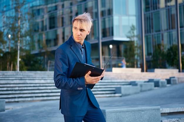 Młody mężczyzna w garniturze z teczką w rękach stoi przed biurowcem
