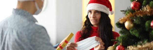 Młody mężczyzna w kapeluszu świętego mikołaja daje prezent kobiecie ochronną maskę na twarz w pobliżu choinki w domu