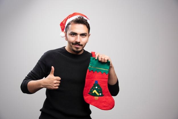 Młody mężczyzna w kapeluszu świętego mikołaja pokazujący kciuk do góry i trzymający świąteczną skarpetę.