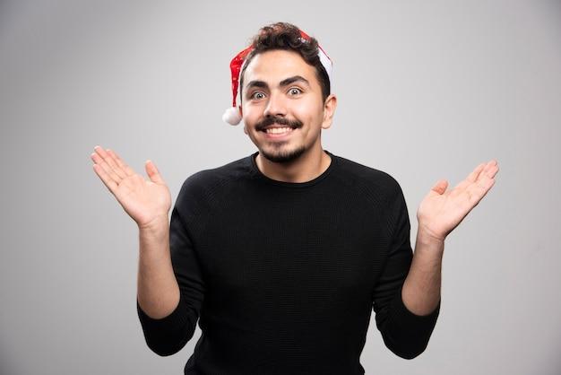 Młody mężczyzna w kapeluszu świętego mikołaja trzymający w rękach coś niewidzialnego.