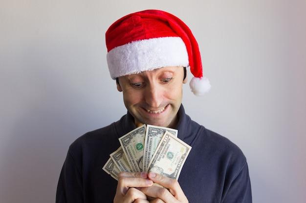 Młody mężczyzna w kapeluszu świętego mikołaja trzymający wachlarza dolara z chciwym spojrzeniem na białym tle nowy rok cel