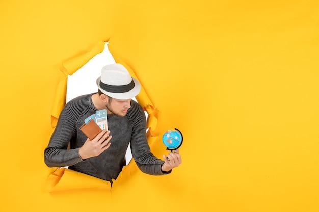 Młody mężczyzna w kapeluszu trzymający paszport zagraniczny z biletem i małą kulą ziemską w rozdartej na żółtej ścianie