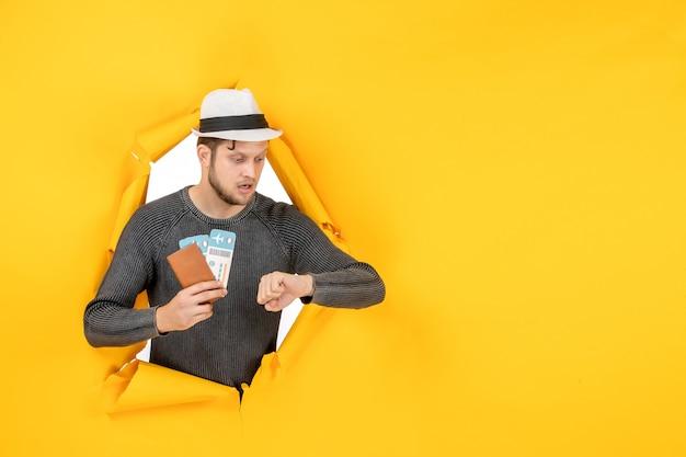 Młody mężczyzna w kapeluszu trzymający zagraniczny paszport z biletem i sprawdzający swój czas w rozdartej na żółtej ścianie