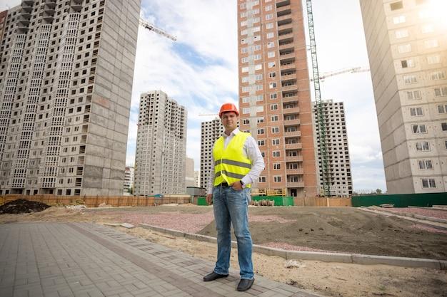 Młody mężczyzna w kasku i kamizelce odblaskowej stojący na placu budowy