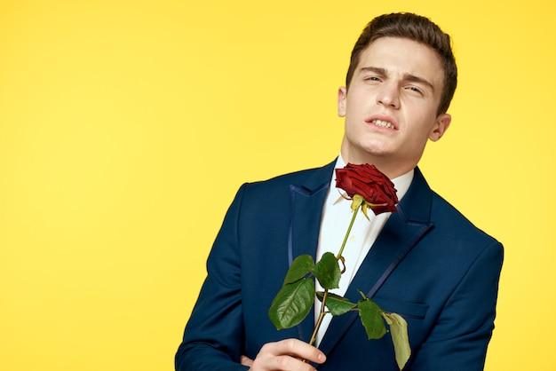 Młody mężczyzna w klasycznym garniturze z różą w dłoniach, seksowny wygląd