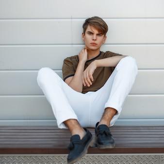 Młody mężczyzna w klasycznym t-shircie i białych spodniach w skórzanych czarnych butach siedzi pod metalową ścianą