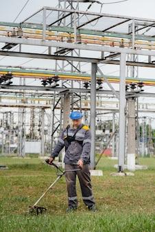 Młody mężczyzna w kombinezonie koszący trawę na terenie podstacji elektrycznej. czyszczenie trawy w przedsiębiorstwie, wdrożenie środków ochrony przeciwpożarowej.