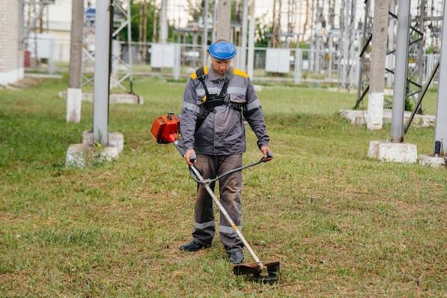 Młody mężczyzna w kombinezonie koszący trawę na terenie podstacji elektrycznej. czyszczenie trawy w przedsiębiorstwie, wdrożenie zabezpieczeń przeciwpożarowych.