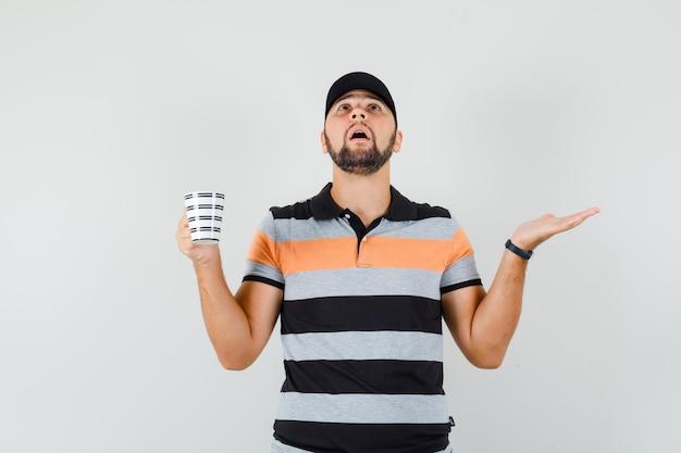Młody mężczyzna w koszulce, czapce trzymającej kubek z napojem, odsuwając dłoń na bok i wyglądający na zaniepokojonego, widok z przodu.